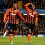 Luiz Adriano y William celebran un gol durante en un partido de Champions League.